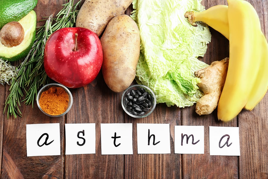 asthma spelled out on a wooden background next to fruit and vegetables