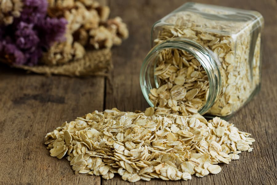 Oat flakes or oatmeal in glass bottle on rustic wood table.