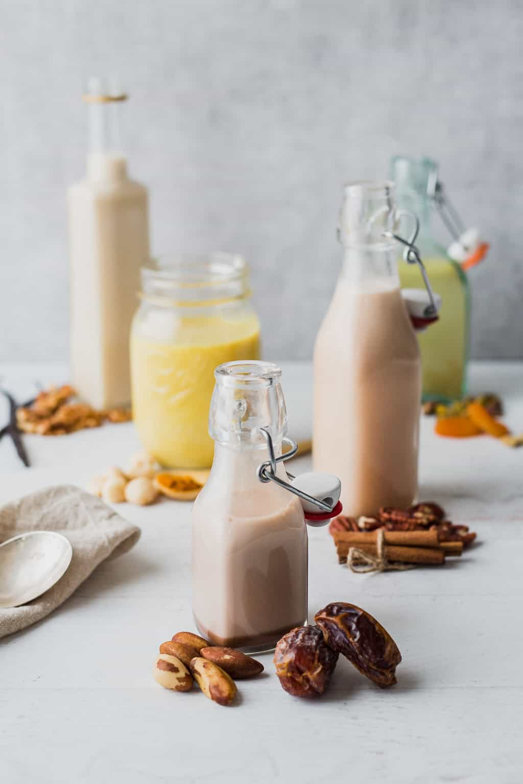 nut milks flavored with spices in jars and surrounded by the nuts they were made with