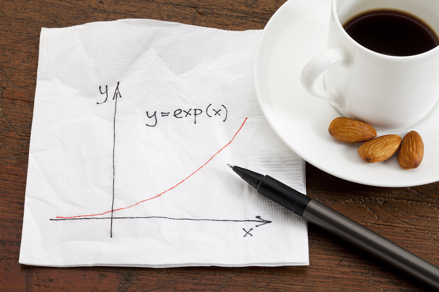 exponential growth curve sketched on a cocktail napkin with coffee cup and snack on wood table