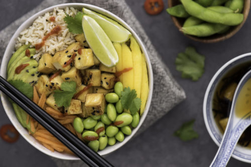 a vegan poke bowl with tofu and lime and mango and rice and edamame