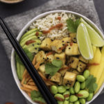 vegan poke bowl with mango and lime and edamame against a dark background with chopsticks